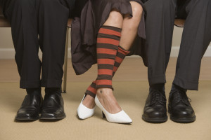 Legs of seated businessmen and woman wearing leg warmers