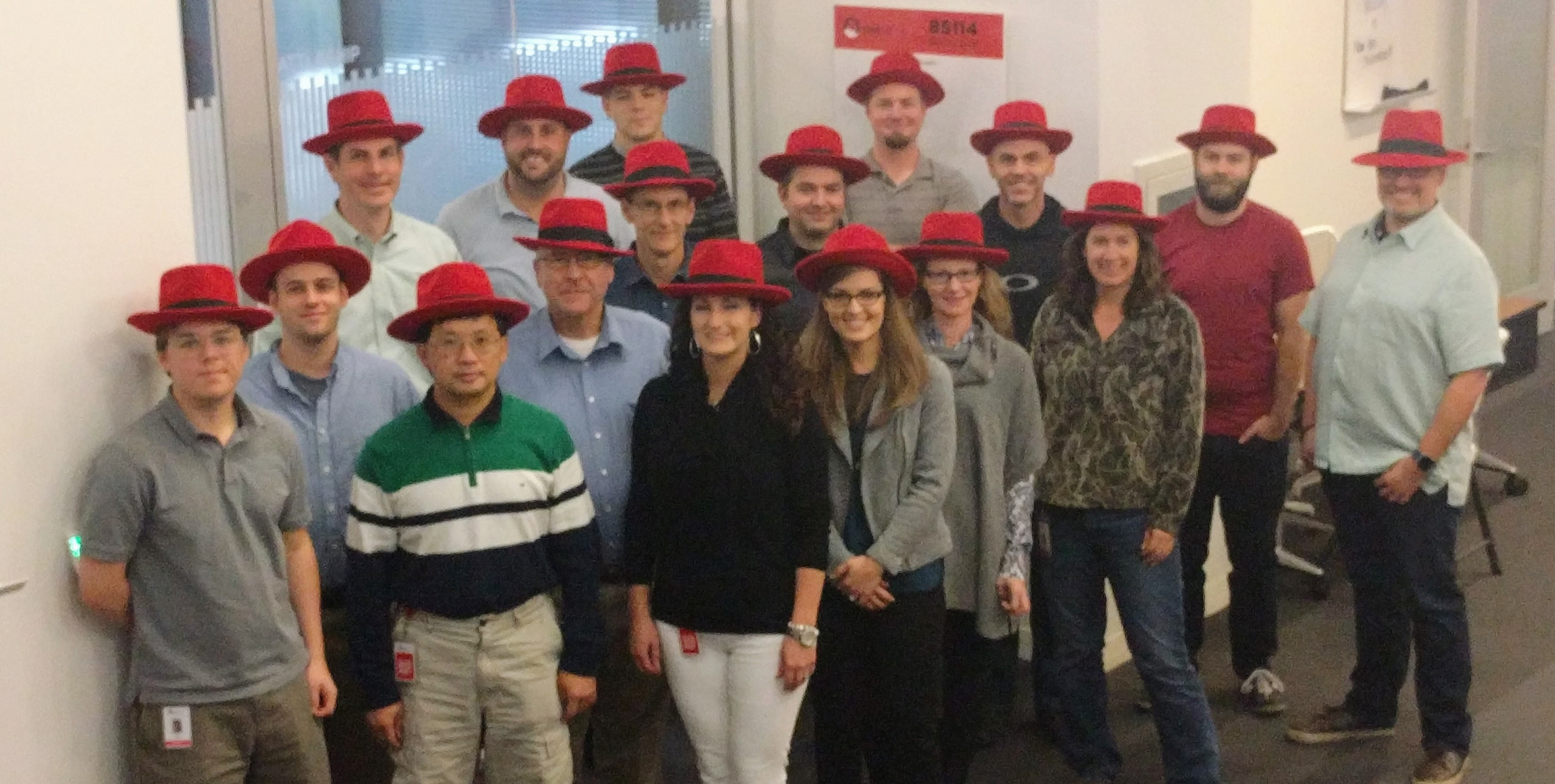 Picture of group of new hires wearing red fedoras.